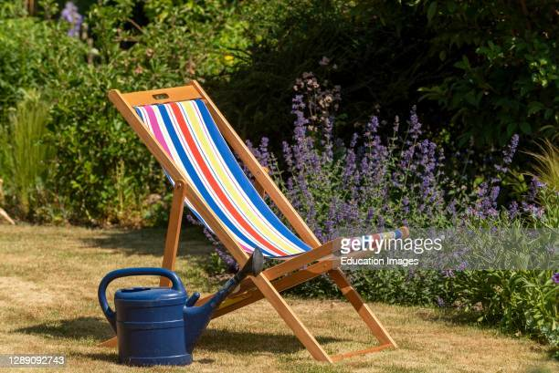 Hampshire, England UK, An open colorful deckchair in an English country garden.