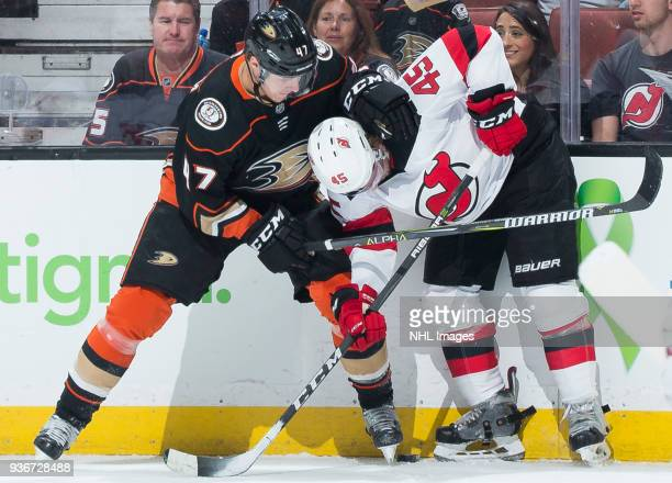 Hampus Lindholm of the Anaheim Ducks and Sami Vatanen of the New Jersey Devils battle for the puck against the boards during the first period of the...