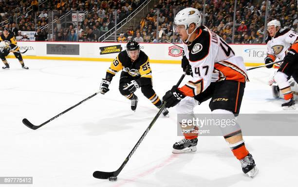Hampus Lindholm of the Anaheim Ducks handles the puck against Jake Guentzel of the Pittsburgh Penguins at PPG Paints Arena on December 23 2017 in...