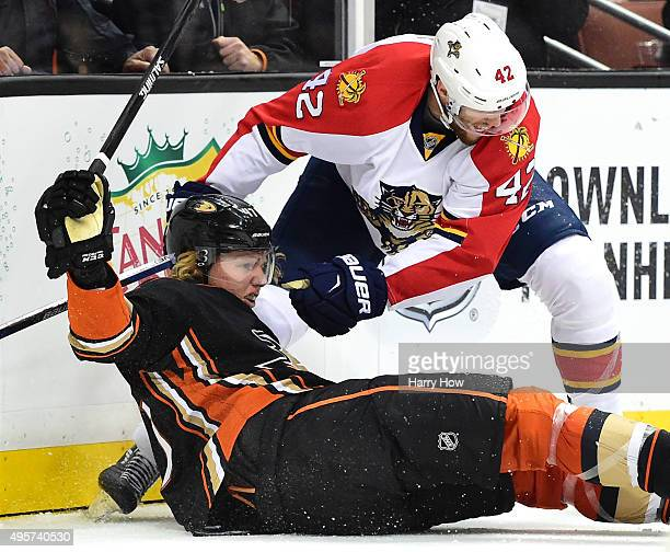 Hampus Lindholm of the Anaheim Ducks is knocked to the ice by Quinton Howden of the Florida Panthers during the second period at Honda Center on...