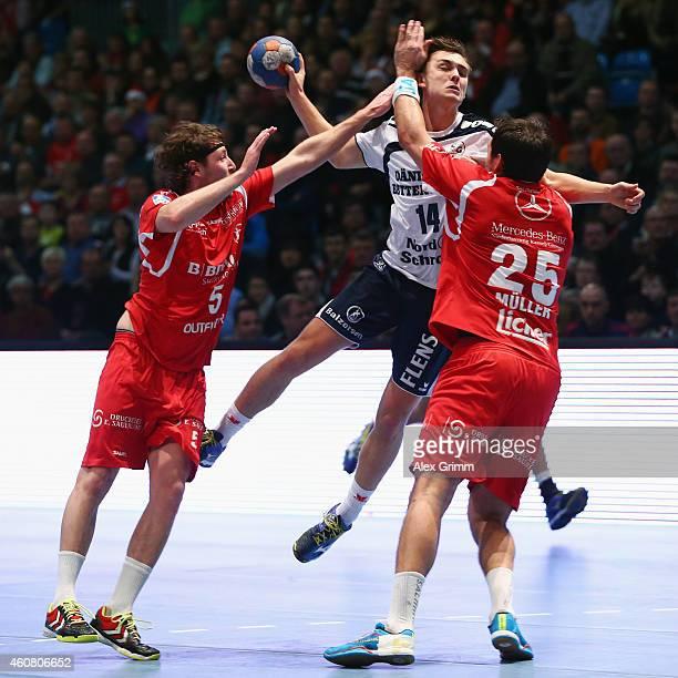 Hampus Wanne of FlensburgHandewitt is challenged by Johannes Sellin and Michael Mueller of Melsungen during the DKB Handball Bundesliga match between...