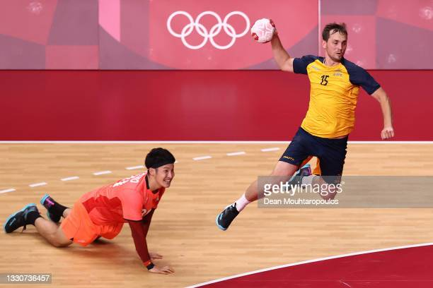 Hampus Wanne of Team Sweden shoots at goal as Tatsuki Yoshino of Team Japan looks on after falling during the Men's Preliminary Round Group B match...