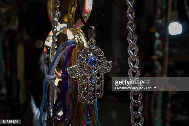hamsa and jewelry hanging for sale at market stall - hand of fatima stock photos and pictures