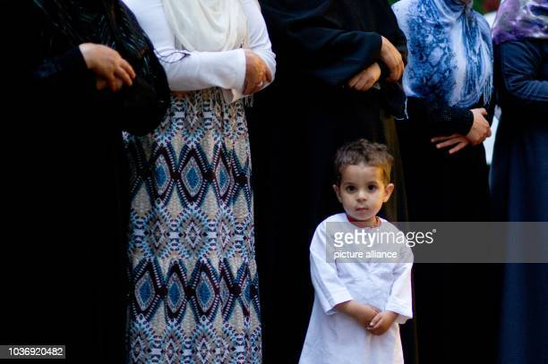 Hamsa stands in front of Muslim women during an evening prayer at the end of Ramadan at the long night of encounters in Hanover Germany 25 July 2013...
