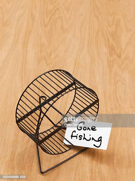 Hamster wheel with 'gone fishing' sign on wooden floor, close-up