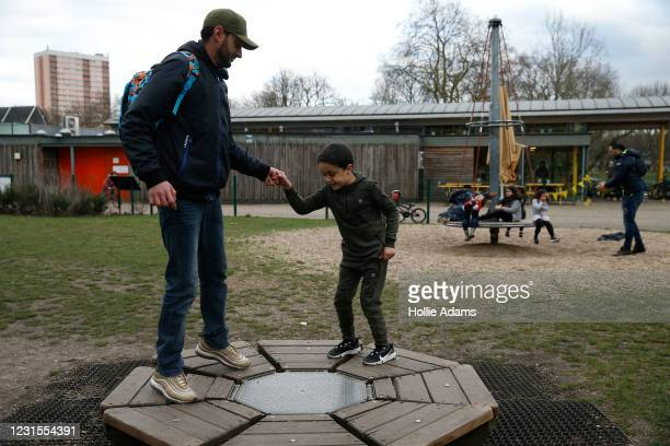 Hamza Abbor, with his son Sofian at Victoria Park playground on March 6, 2021 in London, England. Londoners are enjoying bright weather as end of...