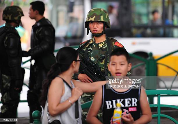 A Han Chinese woman looks over her shoulder at an armed security personnel manning his position while on patrol in Urumqi on July 17 2009 in...