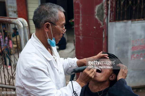 Han dentist at work on a Yi patient in the Yi market of Tuo Mu Guo in Puge County Daliangshan Sichuan China