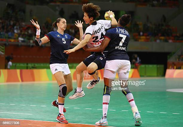 Han Na Gwon of Korea is challenged by Camille Ayglon Saurina of France and Allison Pineau of France during the Womens Preliminary Group B match...