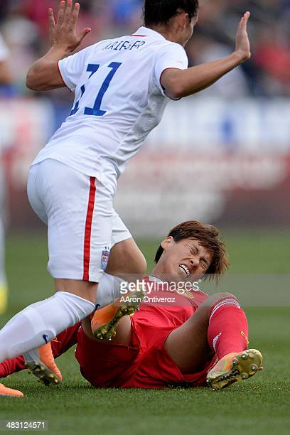 Han Peng of China falls the ground as Ali Krieger of the USA pulls her hands back to indicate she did not make contact during the first half of...