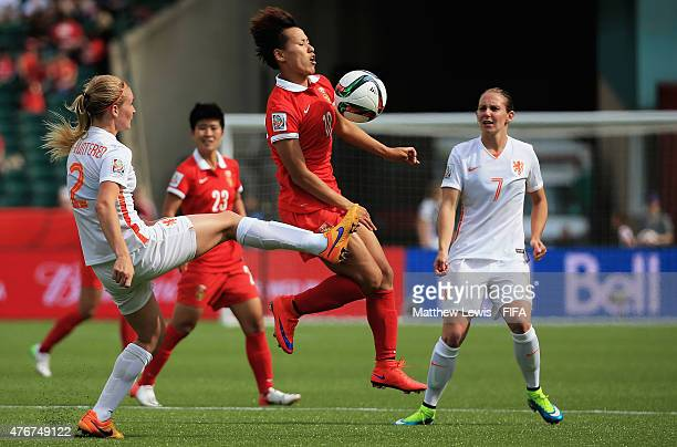Han Peng of China PR wins the ball ahead of Desiree Van Lunteren of Netherlands during the FIFA Women's World Cup 2015 Group A match between China PR...