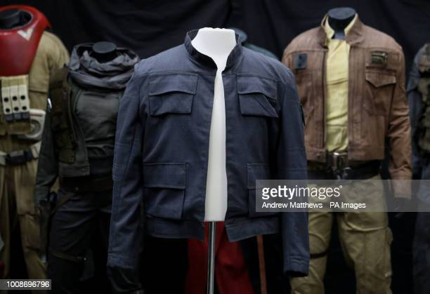 Han Solo's jacket as worn by Harrison Ford in Star Wars The Empire Strikes Back on display in front of costumes from Rogue One A Star Wars story on...