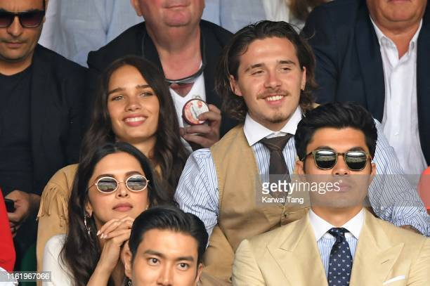 Hana Cross Brooklyn Beckham and Henry Golding on Centre Court on Men's Finals Day of the Wimbledon Tennis Championships at All England Lawn Tennis...