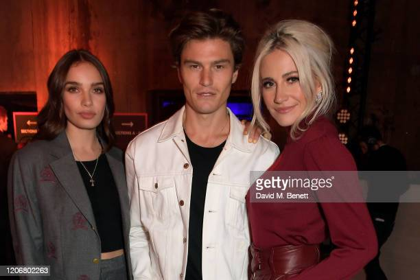 Hana Cross Oliver Cheshire and Pixie Lott attend the TOMMYNOW London Spring 2020 at Tate Modern on February 16 2020 in London England