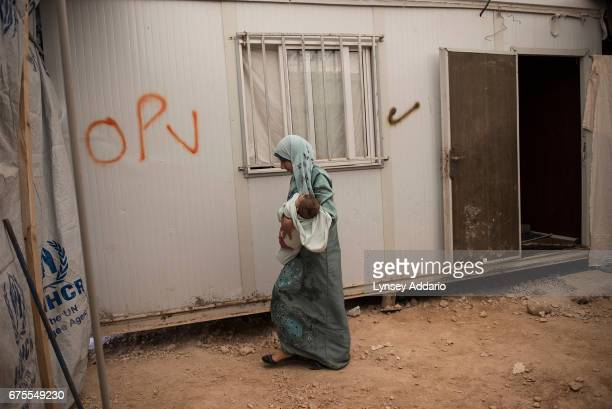 Hana Mufleh Mohammed a Syrian refugee from Daraa leaves her trailer with her five month old baby for the clinic run by JHAS and the United Nations...