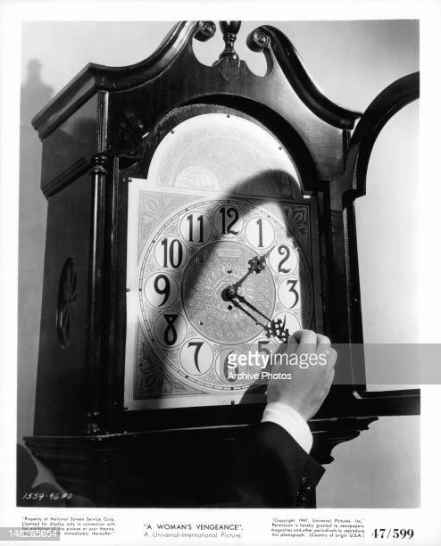 Hand adjusting clock in publicity portrait for the film 'A Woman's Vengeance' 1947