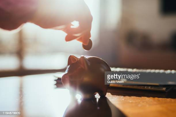 hand and a piggy bank and coin on a table in backlight. - ersparnisse stock-fotos und bilder