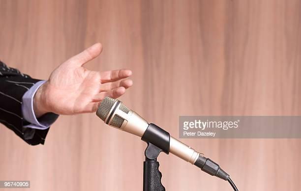 hand and microphone against wooden background. - democracia imagens e fotografias de stock