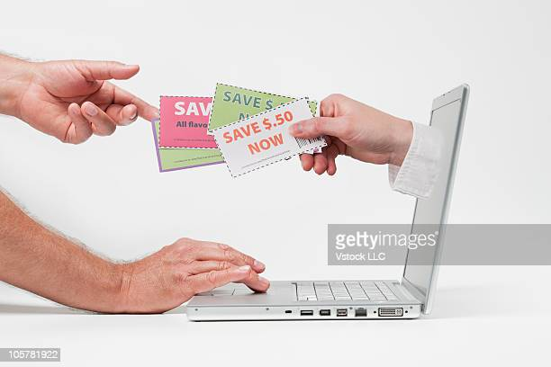 Hand and shopping coupons emerging from laptop