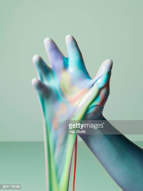 Hand and slime on color blocked background