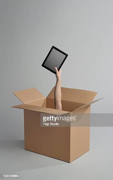 Hand appearing from a cardboard box has digital ta