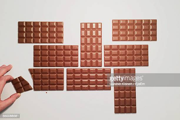 Hand Arranging Chocolate Bars On White Background