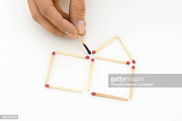Hand arranging matches, holding one burnt match