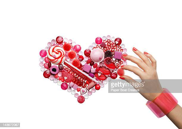hand arranging red and pink heart made of sweets