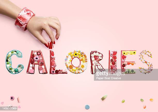 hand arranging sweets and candy spelling calories - font stock-fotos und bilder