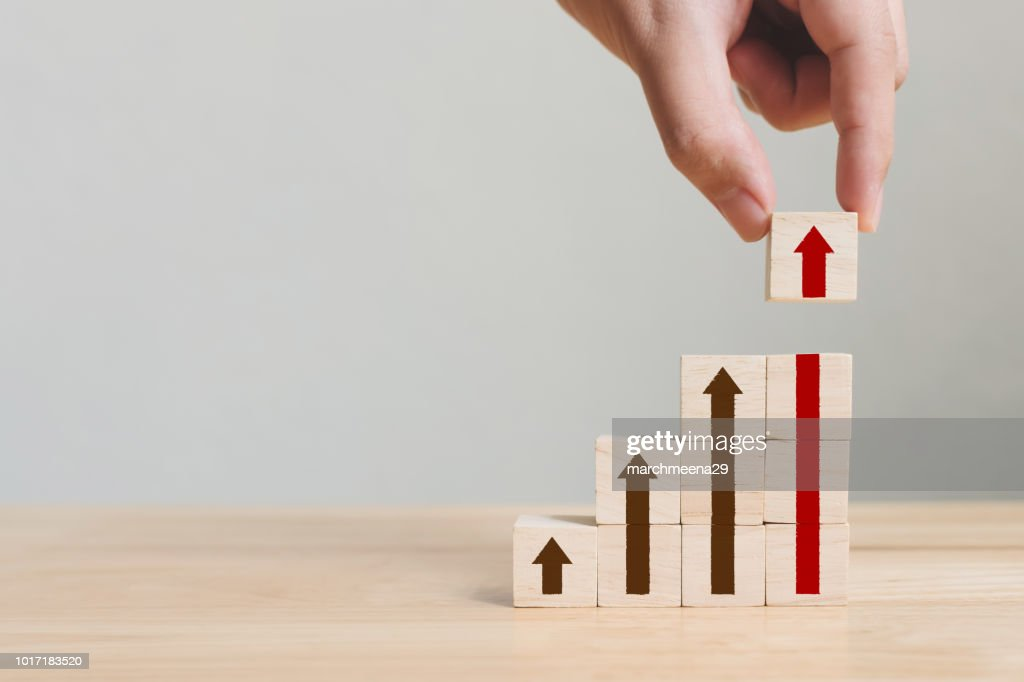 Hand arranging wood block stacking as step stair with arrow up. Ladder career path concept for business growth success process : Stock Photo