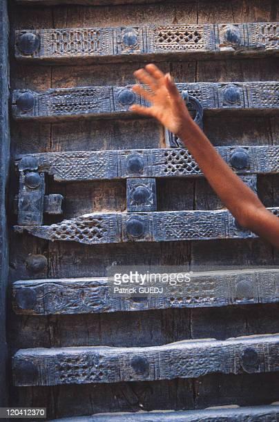 Hand before a sculpted door in Shibam Yemen Book Fleur de peau p83 It is called the Desert's Manhattan in Southern Yemen