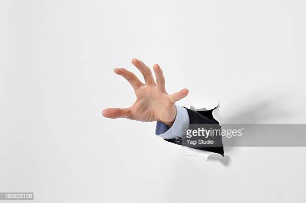 Hand break through the paper