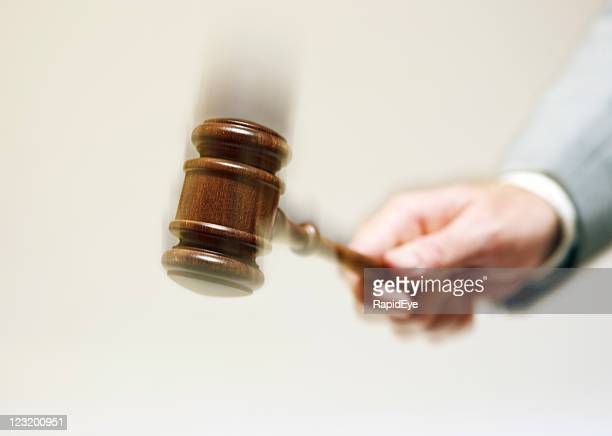 Hand bringing down gavel with exaggerated motion blur