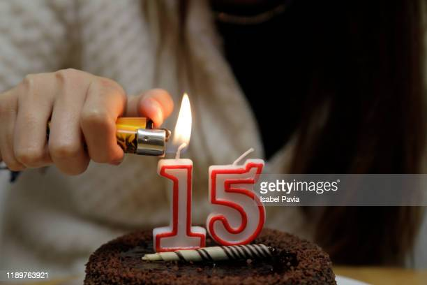 hand burning 15 birthday candles with a lighter - 14 15 anni foto e immagini stock
