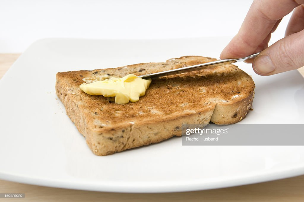 Hand buttering a piece of granary toast : Stock Photo