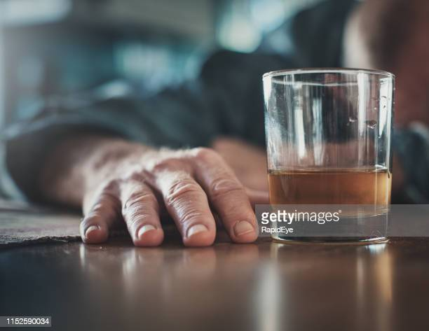 hand by glass of liquor, man's head on table - drunk stock pictures, royalty-free photos & images