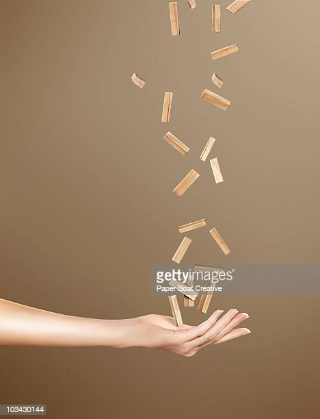Hand catching a bunch of falling wooden blocks