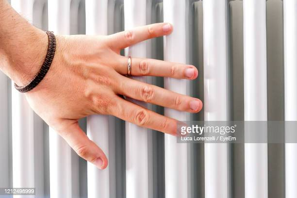 hand check heater temperature radiator closeup - temperature stock pictures, royalty-free photos & images