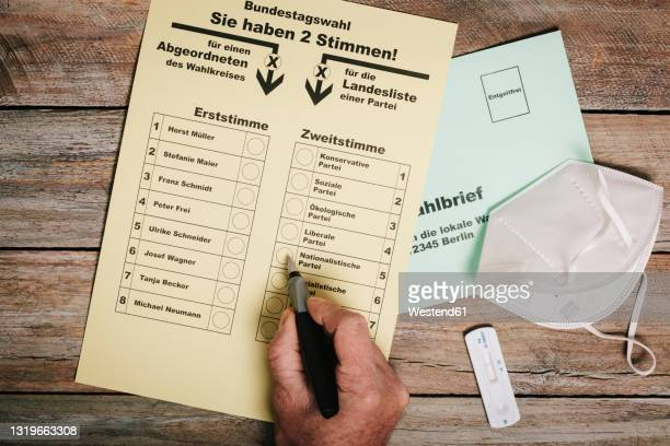 hand checking ballot for federal elections by mail on table with protective mask and corona rapid test - germany stock pictures, royalty-free photos & images
