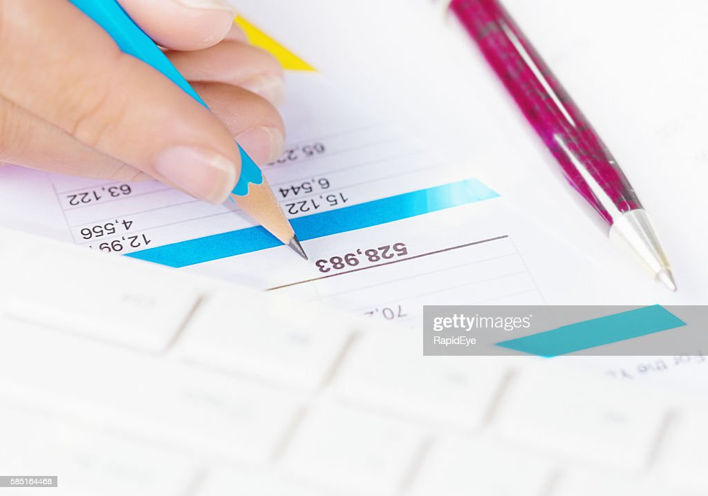 hand checking numbers in financial printout using pencil stock photo