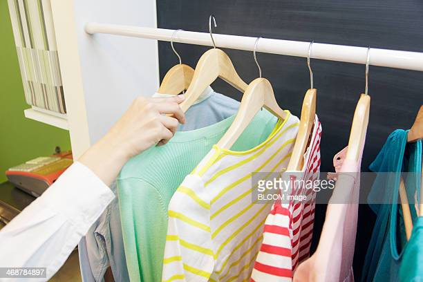 Hand choosing clothes in store