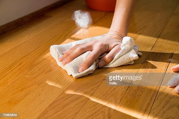 Hand clean wooden floor with rag