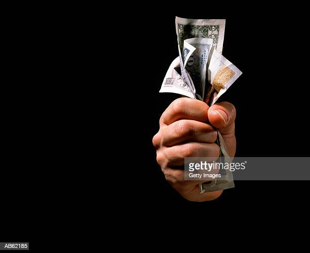 Hand clenching currency, close-up