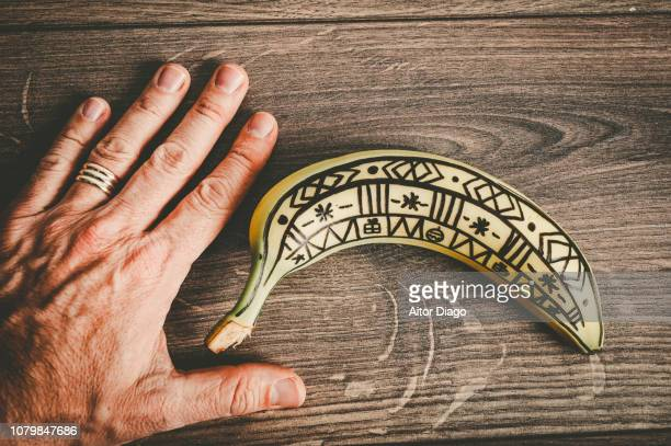 hand close to a painted banana. conceptual nature - darmkrebs stock-fotos und bilder