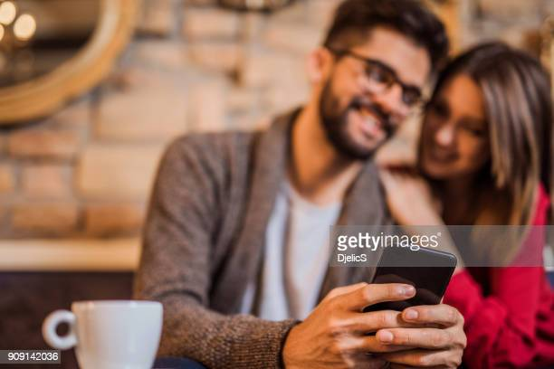 Hand close-up of young couple looking at phone together in a coffee shop.