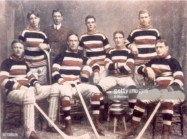 Hand colored group portrait of the famed Canadian hockey team the Ottawa Silver Seven as they pose with the Stanley Cup, 1905. From left, Canadian...