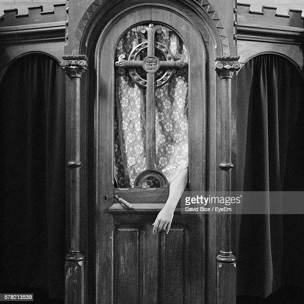 Hand Coming Out Of Confession Booth At Church