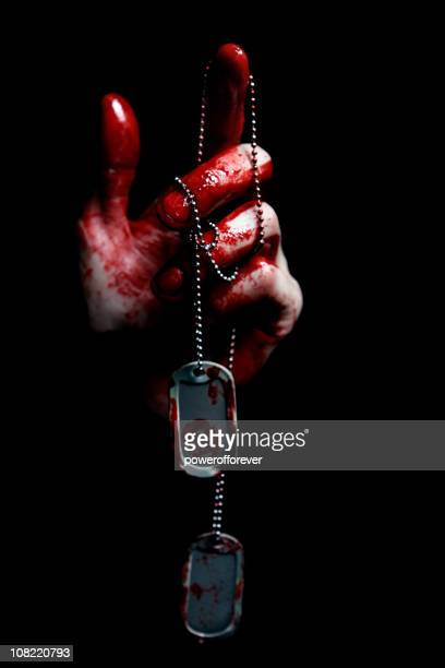 Hand Covered in Blood Holding Dog Tags