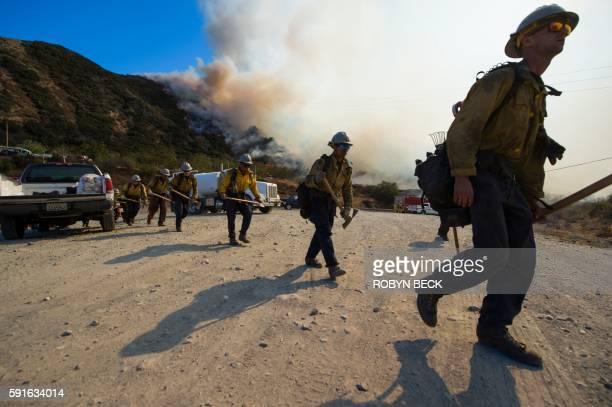 A hand crew prepares to clear a hot spot at the Blue Cut Fire near Wrightwood California August 17 2016 / AFP / Robyn BECK