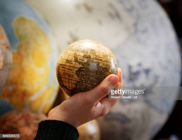 Hand cupping small globe with large globes in background